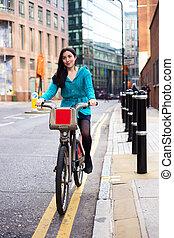 riding a hire bike - young woman riding a hire bike