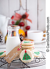 Christmas tree cookies with milk on a cooling rack