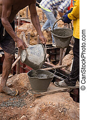 worker pouring concrete from pail bucket