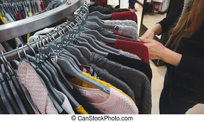 Shopping woman Hands of shopper looking at clothes in...