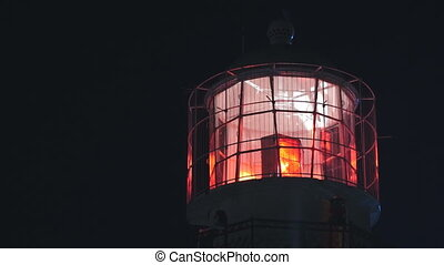 Lighthouse with red light at night, close up shot. Static, slow motion 60 fps.