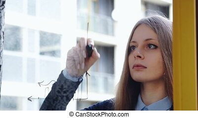 Lifestyle: beautiful young woman drawing math business graphs on the glass with skyscraper on background. Close-up shot, static.