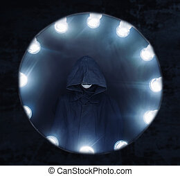 Human in a raincoat surrounded by light lamp, Halloween or...