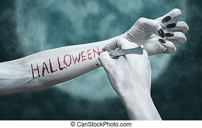 Writing Halloween on arm - Unrecognizable dead woman writes...