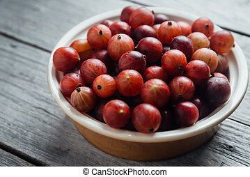 Red gooseberries in plate on wooden background