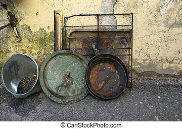 Old ware against a shabby wall - Old rusty ware against a...