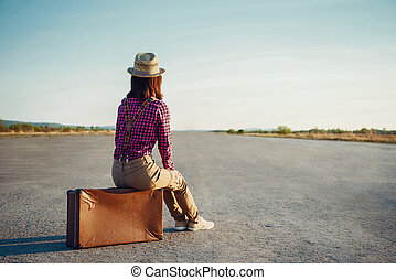 Traveler girl sits on suitcase - Woman sits on retro...