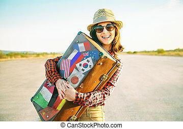 Woman embraces a suitcase - Happy woman traveler embraces a...