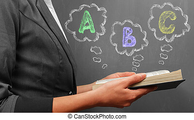 ABC alphabet - Teacher woman in suit reads a book near a...