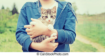 Girl holds kitten - Girl holds striped little kitten outdoor