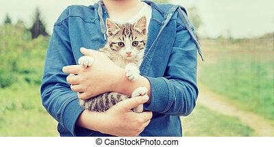 Girl holds kitten - Girl holds striped little kitten outdoor