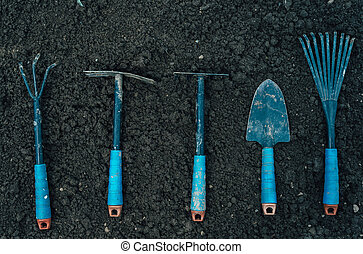 Gardening tools - Different gardening tools on soil, top...