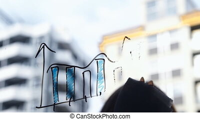 Lifestyle: beautiful young woman cleaning math business graphs from the glass with skyscraper on background. Southpaw. Close-up shot, static, slow motion 60 fps.
