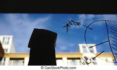 Lifestyle: beautiful young woman cleaning math business graphs from the glass with blue sky, skyscraper on background. Silhouette. Close-up shot, handheld.