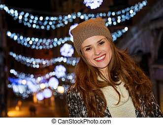 Woman standing in the front of Christmas lights in the...