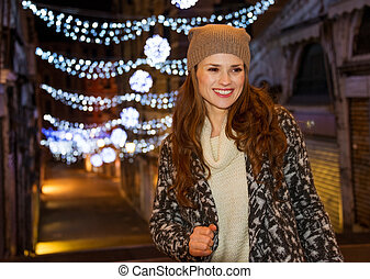 Stylishly dressed woman standing in front of Christmas...