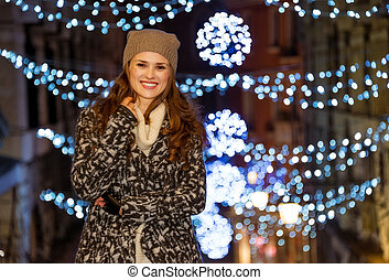 Happy woman standing in front of Christmas lights in evening...