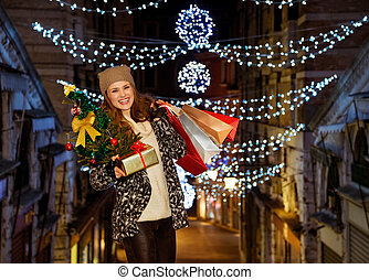 Portrait of woman with Christmas tree, gift and shopping...