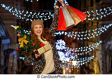 Woman with Christmas tree, gift and shopping bags in Venice...