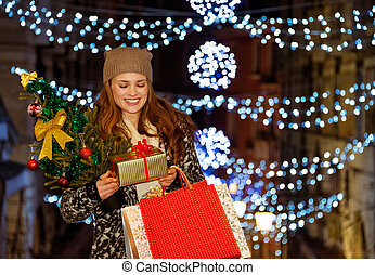 Young woman with gift and shopping bags among Christmas...