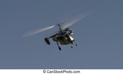 View of helicopter quickly flying over airfield - View of...