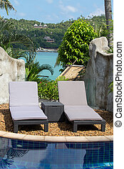 Swimming pool and beach chairs in a tropical garden near the...