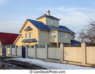 Modern two-storey cottage with blue roof, early spring
