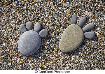 Two trace feet made of a pebble stone on the beach backdrop...