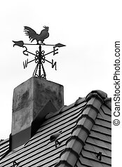 Rooster weather vane on the roof with black tiles