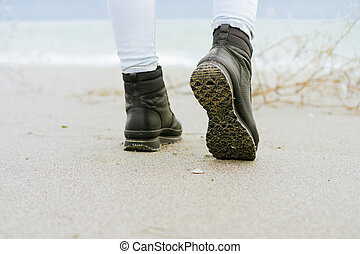 Female feet in blue jeans and black winter boots standing on the beach against the sea