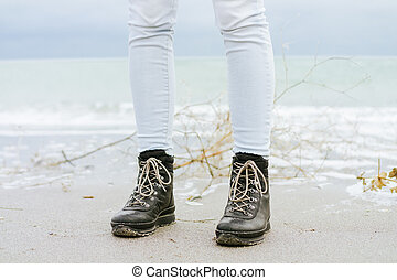 Female feet in blue jeans and black winter boots standing in the sand against the sea