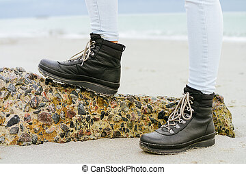 Female feet in blue jeans and black winter boots standing on a stone against the sea