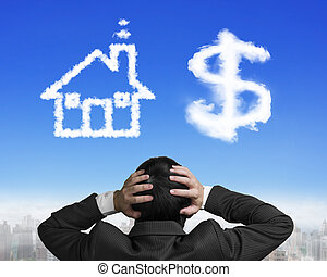Dollar sign house shape clouds with businessman hand holding...