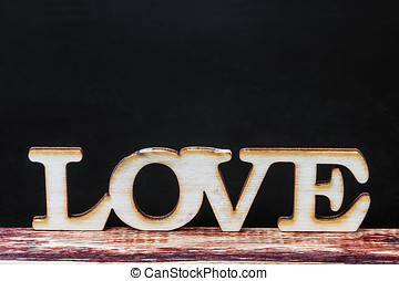 carved wooden letters love. focus on the bottom of the...