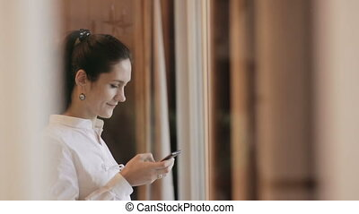 Woman sending messages with phone near the window