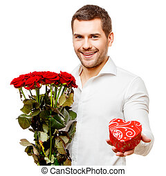 Young man carries heart shaped box and flowers, isolated on...