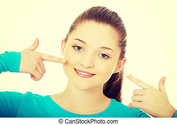 Teenage pointing at toothy smile. - Happy teenage woman...