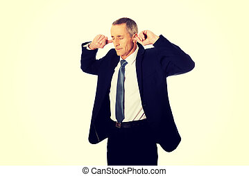Businessman plugging his ears - Mature businessman plugging...