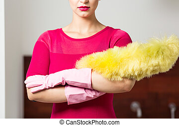 Perfect cleaning lady with feather duster and gloves