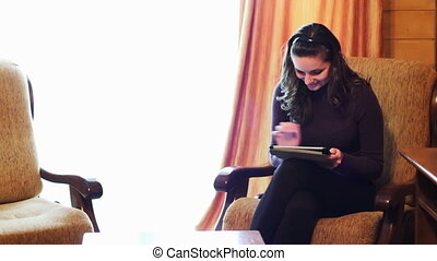 Woman with the tablet on an armchair. - Girl working on a...
