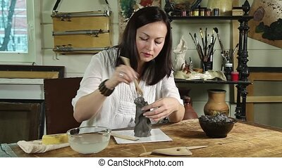 Woman shaping clay sculpture - Artisan woman modelling a...