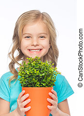 Smiling girl upholding a green plant. - Girl with flower....