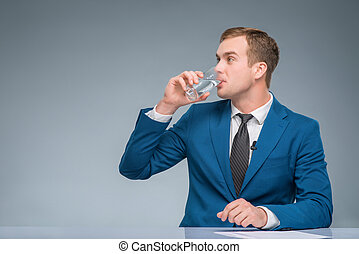Newsman drinking water at his desk. - Gulp of water....