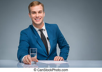 Smiling newsman holding a glass of water - Confident man...