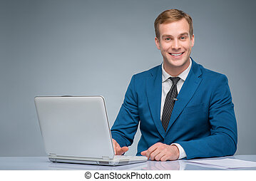 Smiling newsman working with his laptop - Digital...