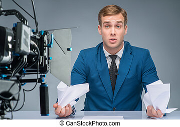 Newsman looks stressed out. - Clutching papers. Handsome...