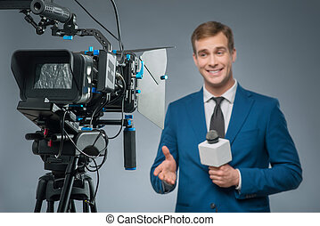 Smiling newsman with a microphone. - Smiling reporter....