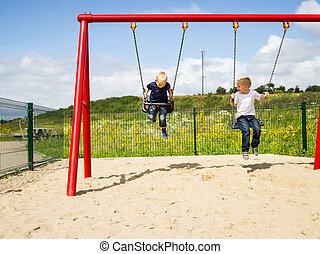 Children boys playing on swing outdoor - Little blonde boys...