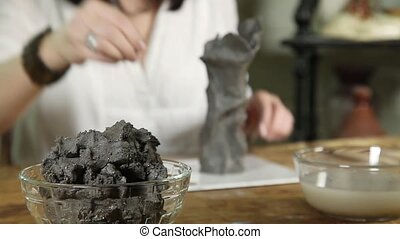 Sculptor shapes the clay with hands close up. Focus on a...