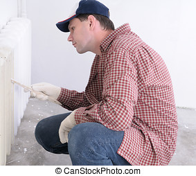 Man painting radiator - Construction worker painting...